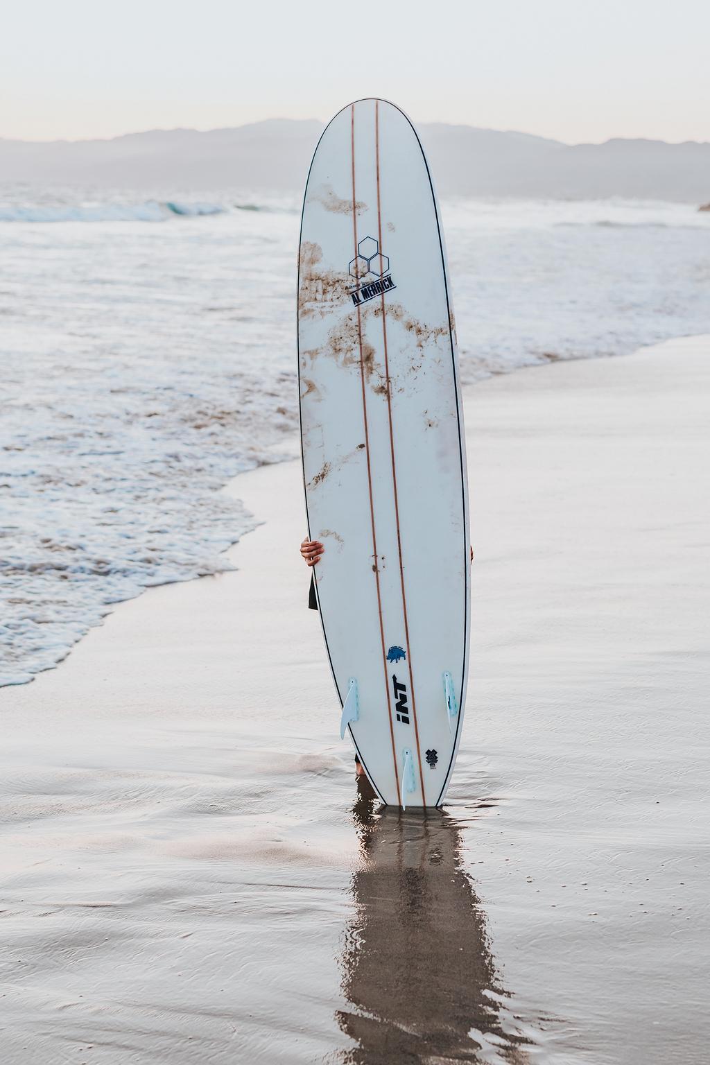 白天在海滨直立的白色冲浪板
