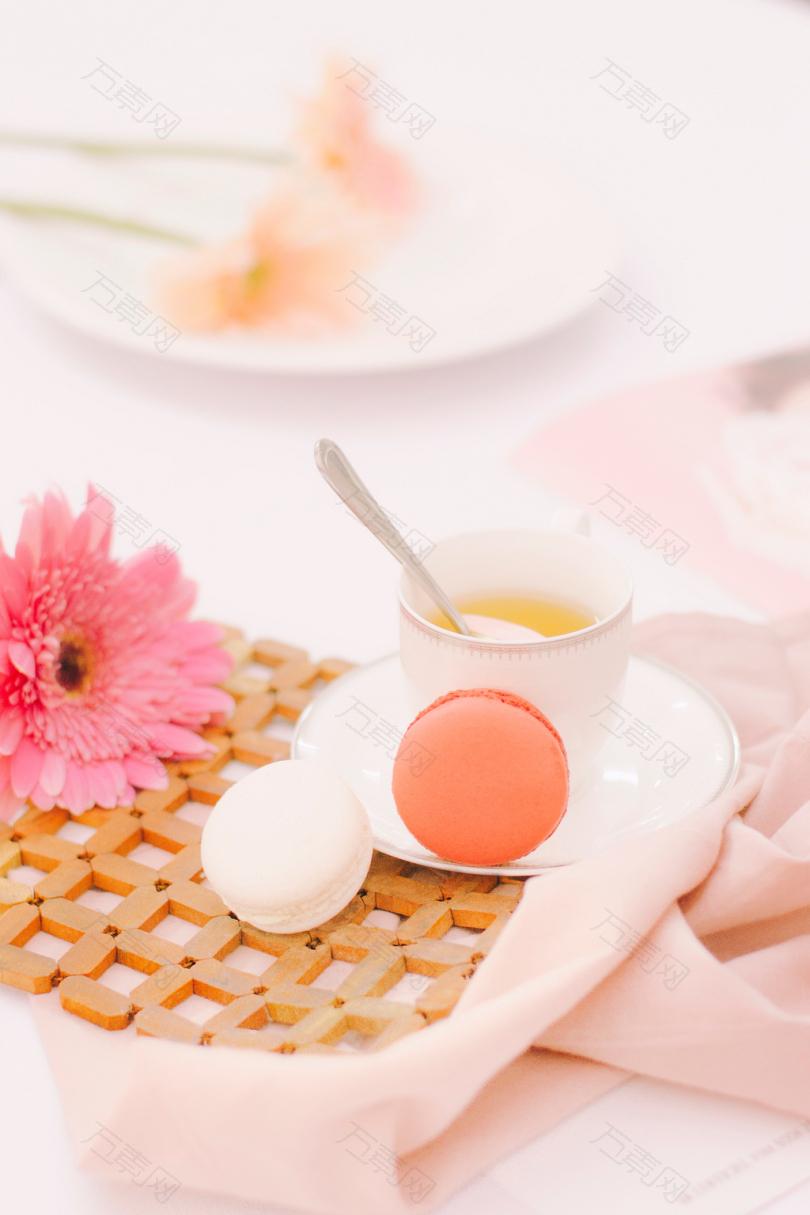 两个橙色和白色的麦卡龙在白色陶瓷杯旁用勺子